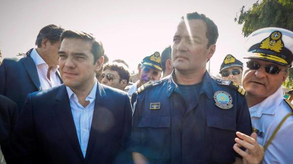 greek-coast-guard-lieutenant-kyriakos-papadopoulos-stands-next-to-greek-prime-minister-alexis-tsipras-during-tsipras-s-visit-to-the-island-of-lesbos